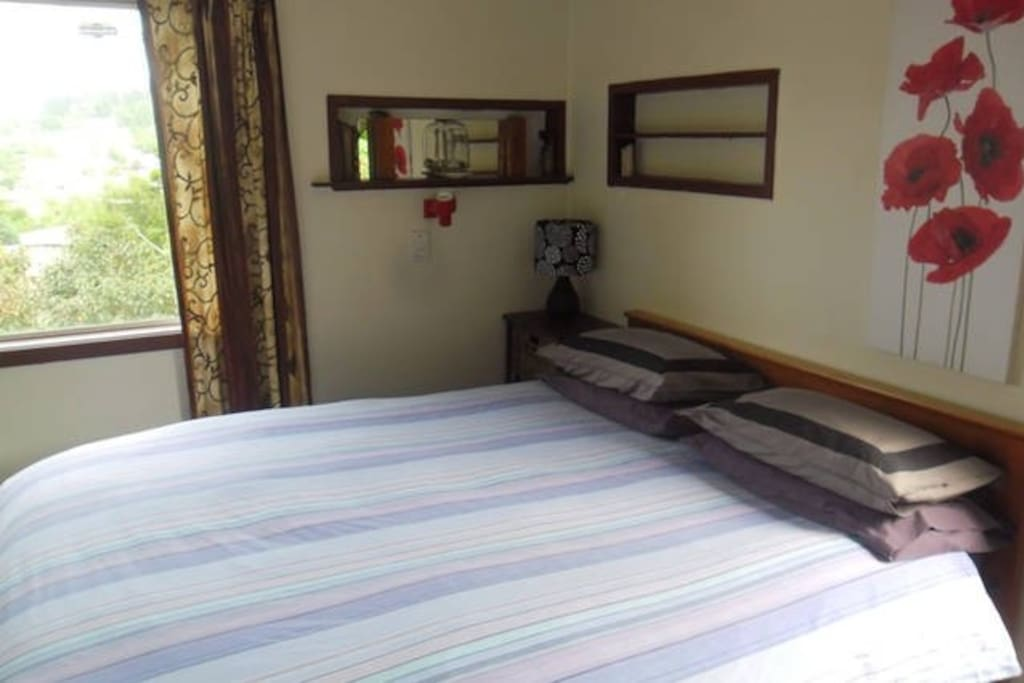 Lovely queen bed in main room.