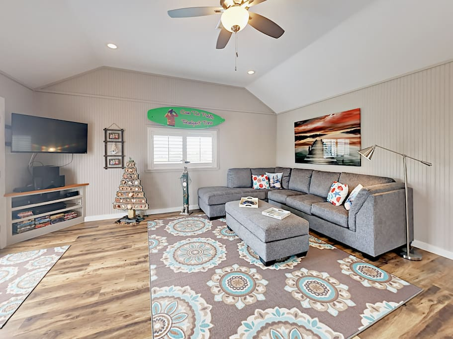 """Relax in the living room on the large sectional sleeper sofa and watch a movie on the 50"""" mounted flat screen TV."""