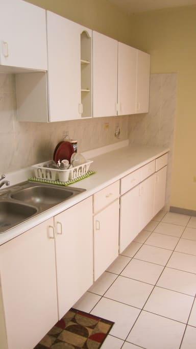 The fully equipped kitchen with stove, fridge and microwave is kept in white, it is large and inviting to prepare your meals.