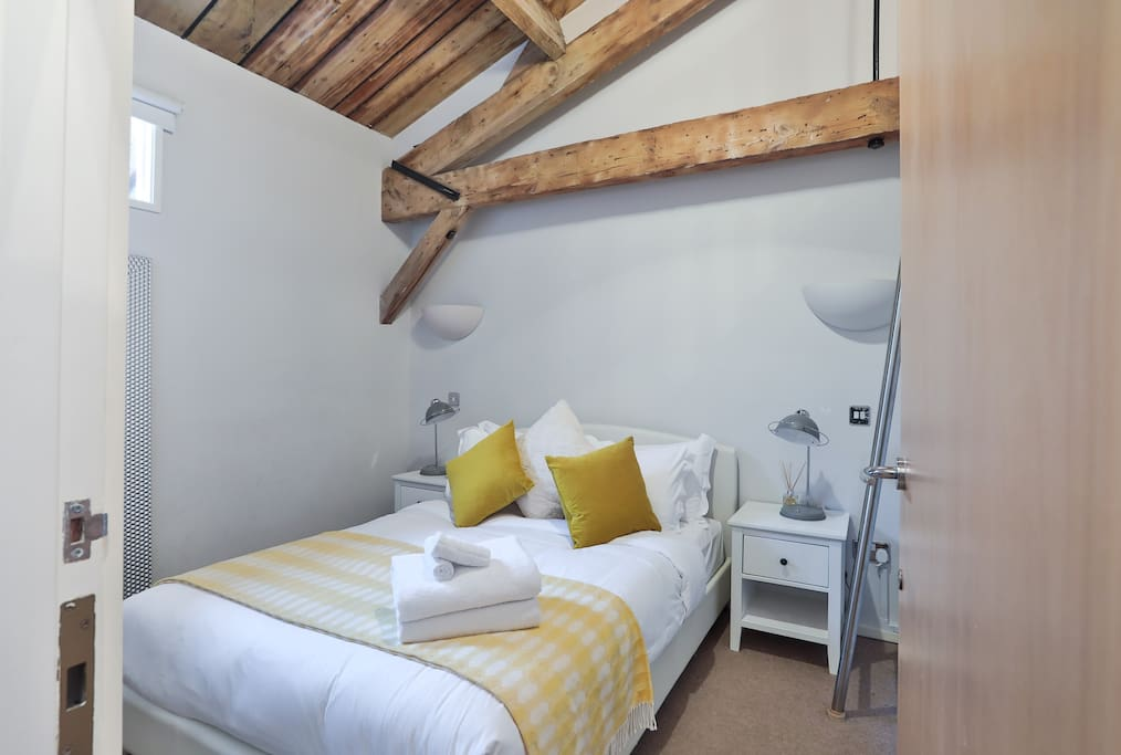 Second double bedroom with additional single guest bed on mezzanine floor, seen to the right of the picture