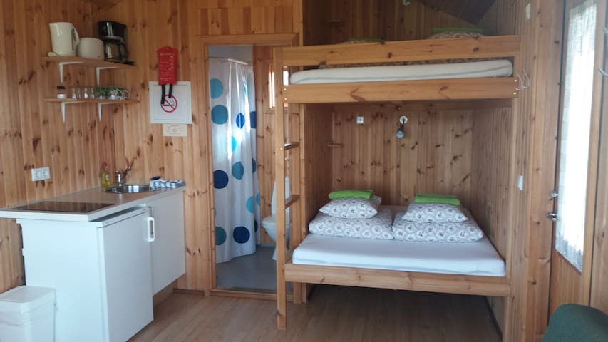 Kitchen with amenities, bathroom and double bunk beds
