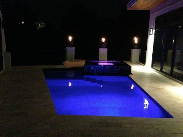 Modern pool and spa in the central courtyard at night.