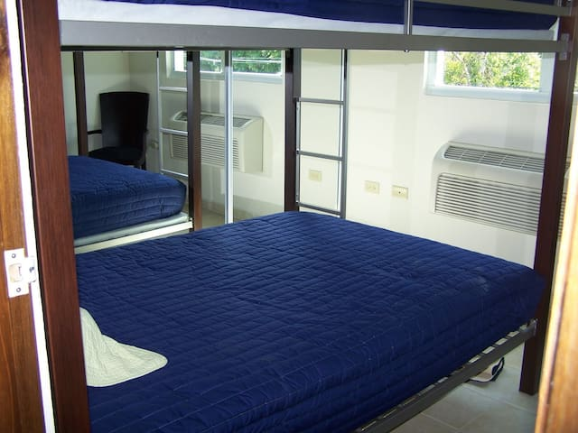 Guest bedroom with full size bunked beds. Room is a bit tight, but the beds sleep 2-4 people comfortably.