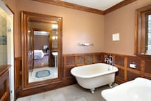 Private bath with clawfoot tub and limestone floor