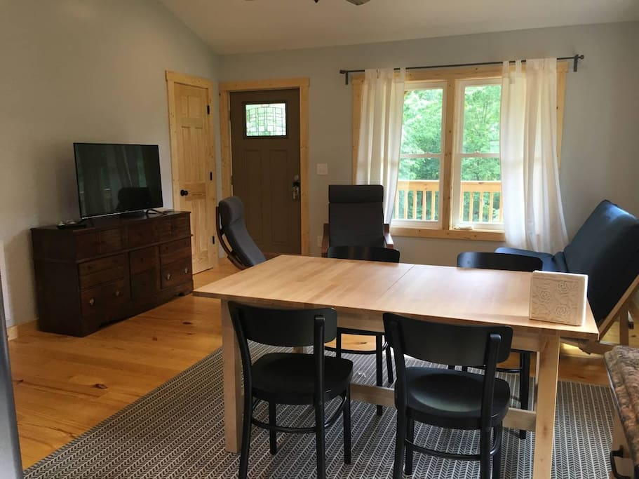 Comfy living room with vaulted ceilings, dining table, futon sofa TV and chairs