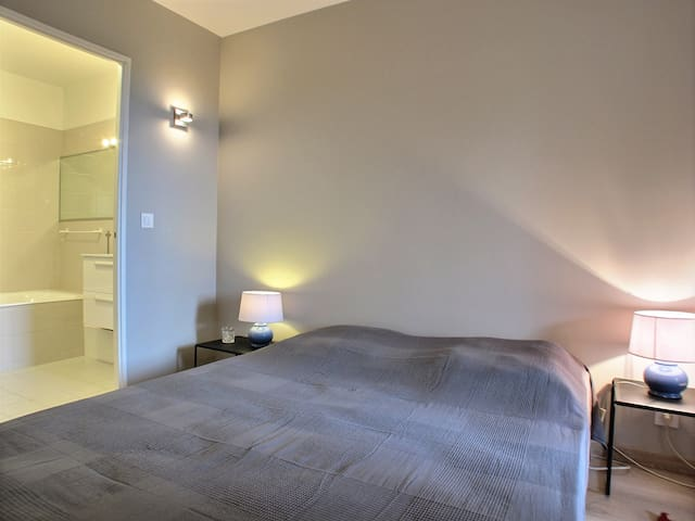 Chambre  donnant sur la terrasse avec lit en 160, placard dressing et étagères de rangement, salle de bain attenante.