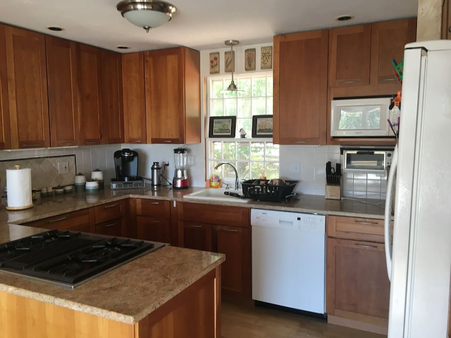 Up-to-date kitchen with dish washer, plenty of plates, cups, bowls... coffee maker/hot water heater, microwave