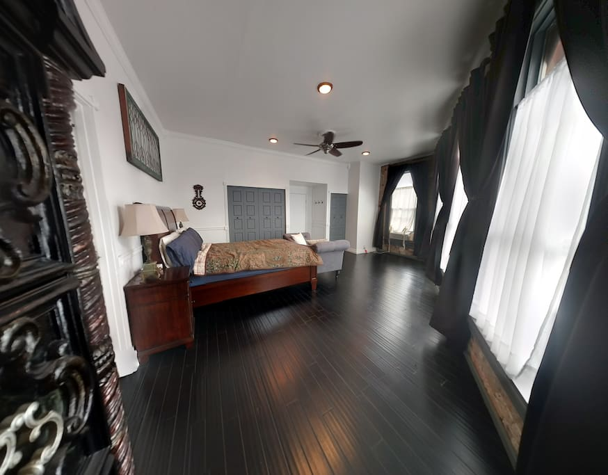 Large Bedroom (350 sq. ft.) with a queen sized bed, settee, four tall windows, heating/air conditioning, ceiling fan, and closet space.