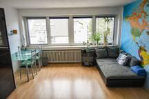 Panoramfenster sorgen für sehr viel Licht im Zimmer. Es ist eine gemütliche Couch sowie ein großer Schreibtisch vorhanden.