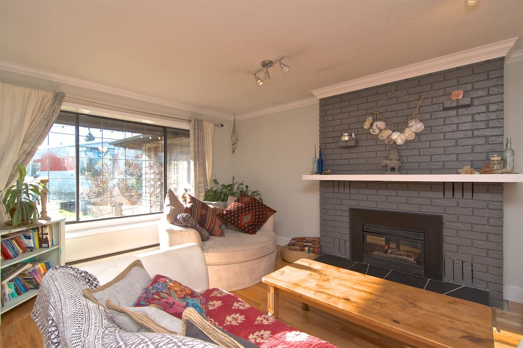 Cozy and open living space with gas fireplace, large comfy round couch perfect for a morning read with a ton of natural light shining through the wall-sized window.