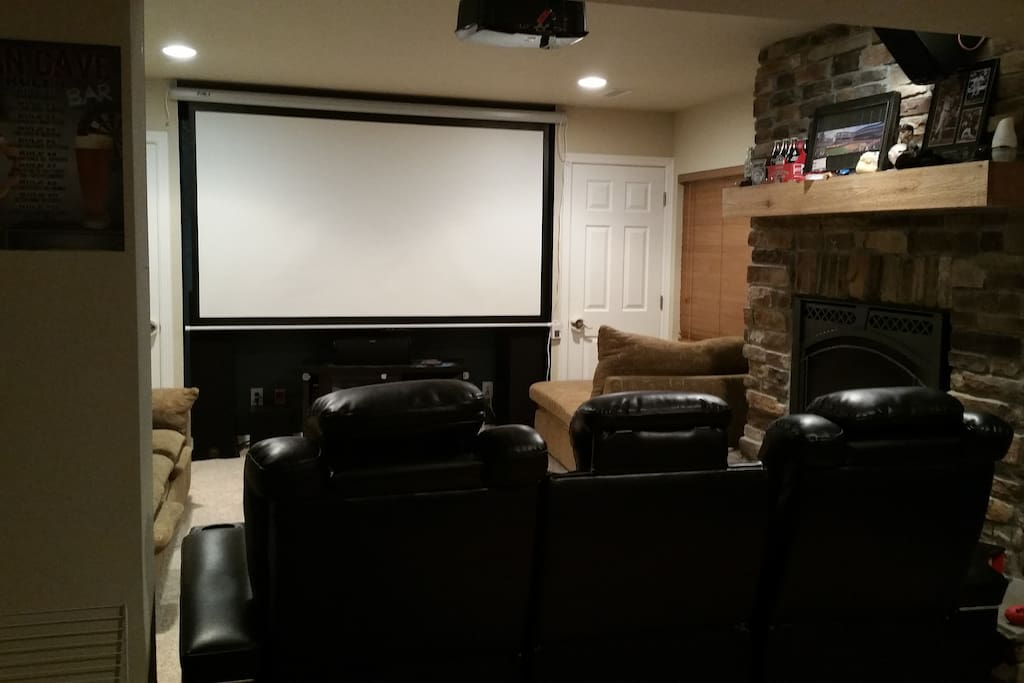 Projector movie room with fireplace and bar area.