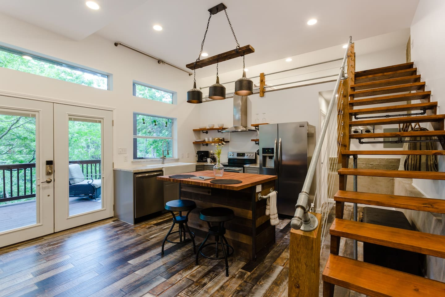 Full kitchen overlooking balcony. Stairs leading up to loft area.