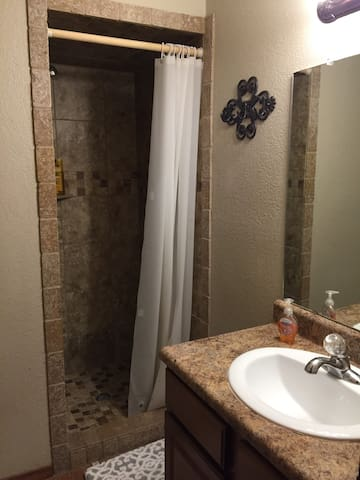 Bath two off bedroom with queen bed.  Travertine tile shower.