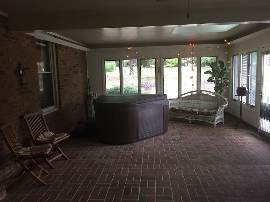 Large enclosed porch area with a jacuzzi.