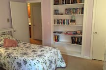 Twin beds, a cozy chair for reading and a bookshelf with summer reads!