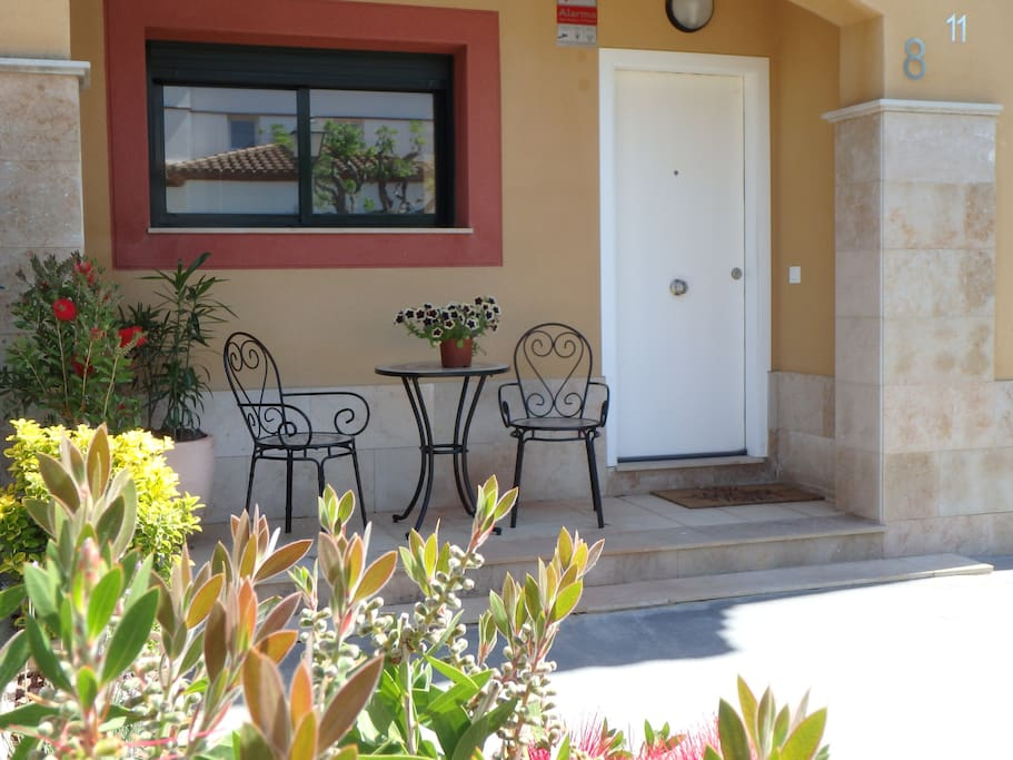 Entrance door and private garden with table plus 2 chairs.