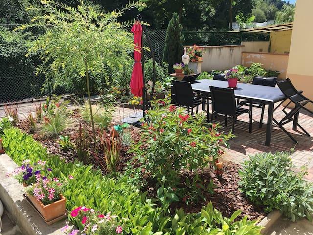 Jardin privatif orienté plein sud au calme avec table ,  chaises et parasol et sa piscine .