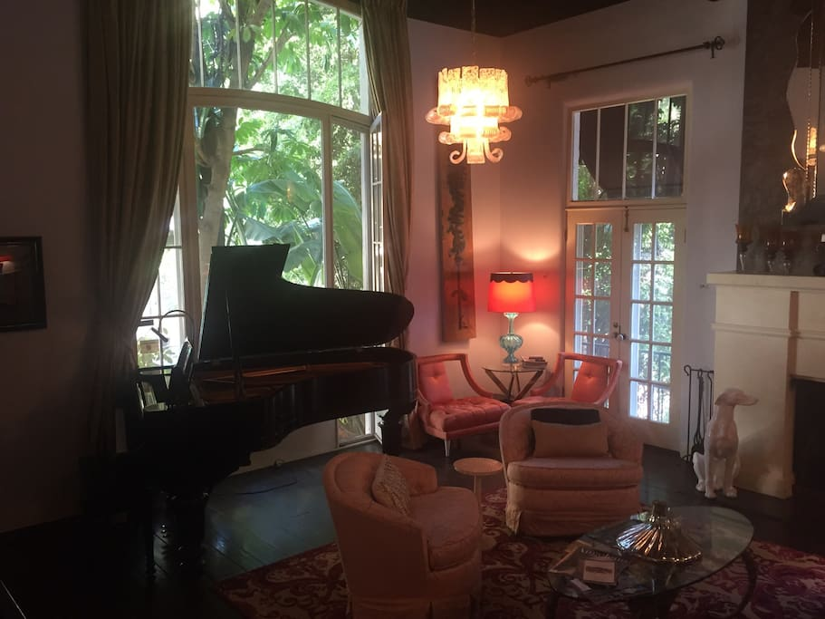Welcome to Hollywood. Living room features a limited edition Steinway piano, a fireplace and a staircase right out of the movies.