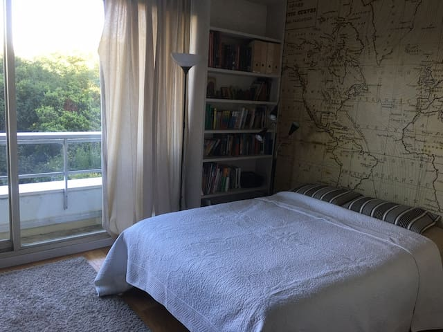 une chambre avec balcon sur petit jardin