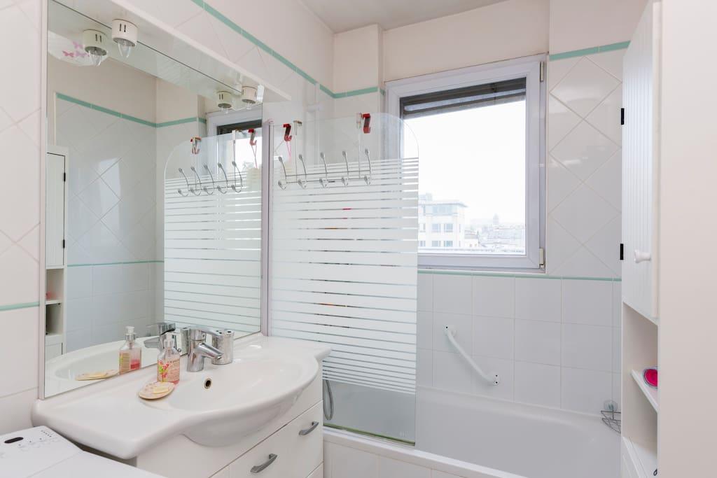 Salle de bains lumineuse avec baignoire et pare douche