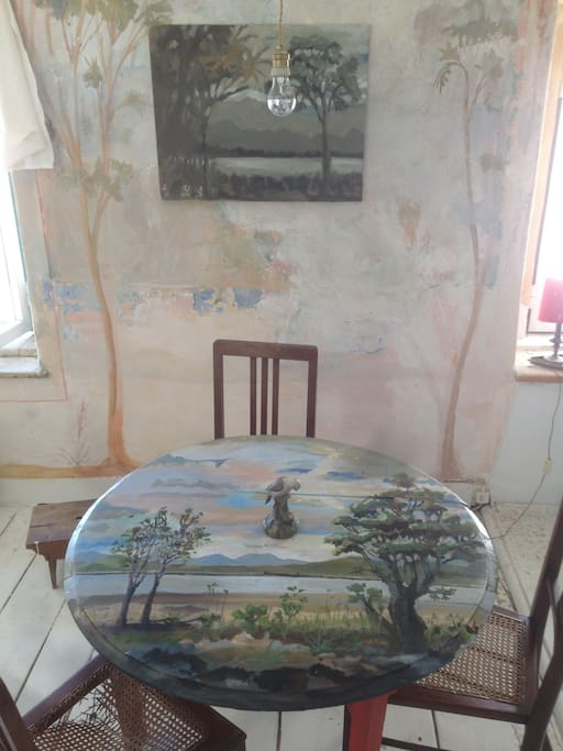 The painted table and wall and painting on the wall...