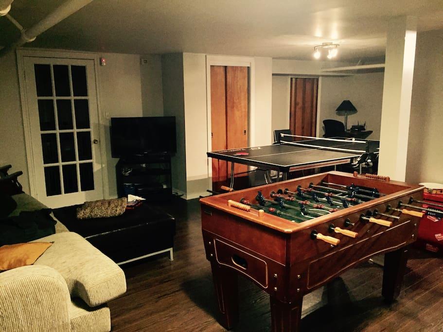 Sous-sol avec table de Ping-pong et table de babyfoot, télévision et sofa