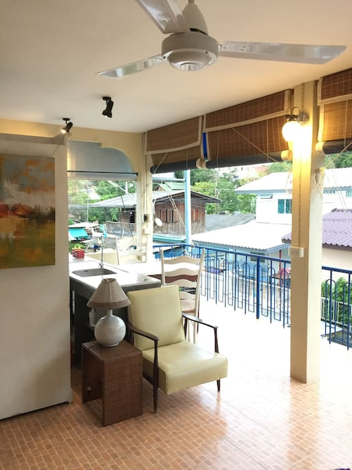 """On the left, the balcony is open to the fisherman village by the sea where walking distance is 50m away.  Guests also have a mountain view of Khaotao (refers to """"Turtle Hill"""") where one can take a short scenic hiking to reach nearby famous Sai Noi Beach. The dining table is good for two but we accommodate two extra portable chairs kept in the closet."""