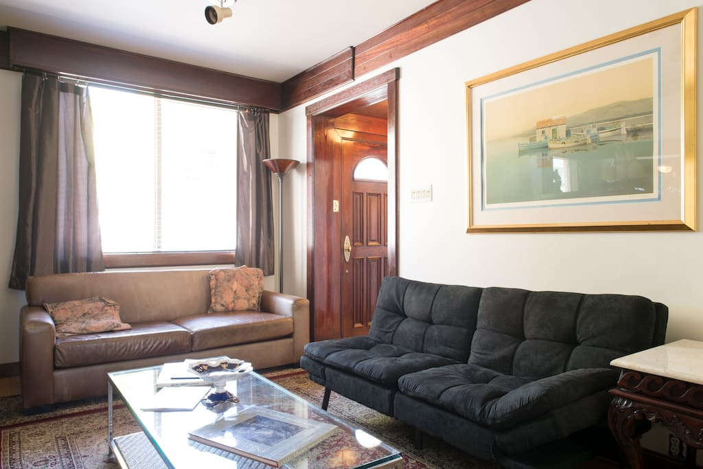 The sofabed is to the right of center. The entrance portico is in the far corner. Unseen within the entrance portico is a floor-to-ceiling mirror and a cedar-lined storage and clothing closet.