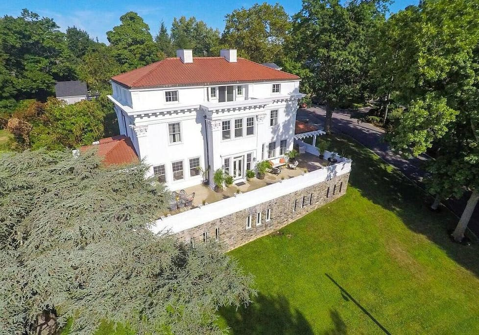 Areal view of back of this Mediterranean Style home with a Spanish tile roof