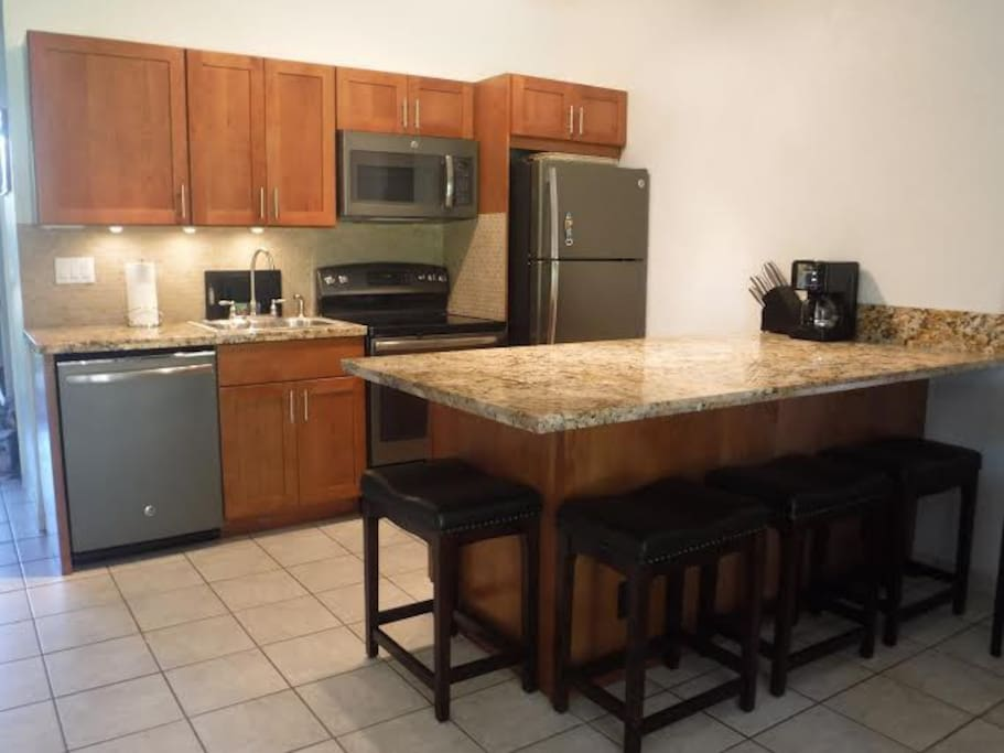 Fully stocked kitchen featuring new appliances, cabinets and granite counters