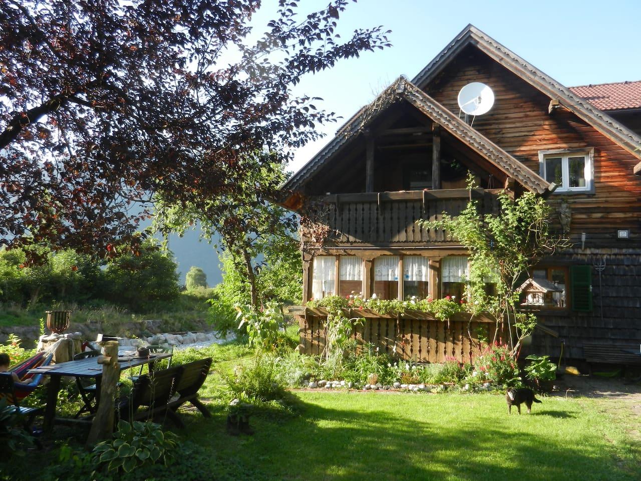 Rustikales Holzhaus mit Garten und Grillmöglichkeit neben einem kleinen Bach.