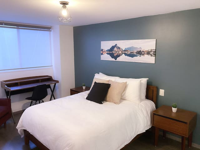 The master bedroom includes a queen-sized bed, a bookshelf, a lounge chair, an office desk, a walk-in closet, and an en-suite bathroom.
