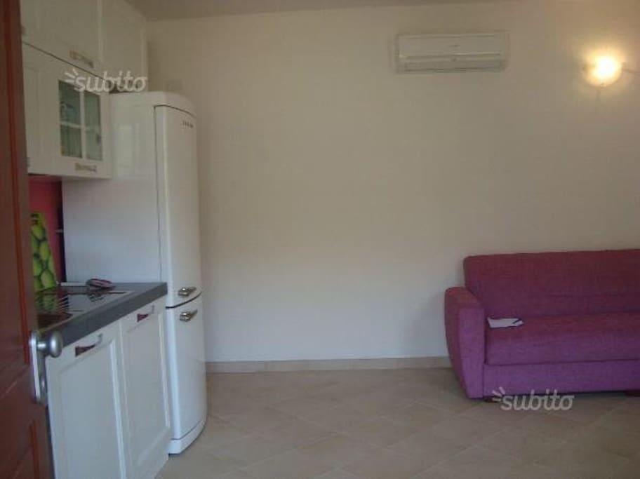 Cucina e soggiorno con divano letto singolo; aria condizionata e TV via cavo.