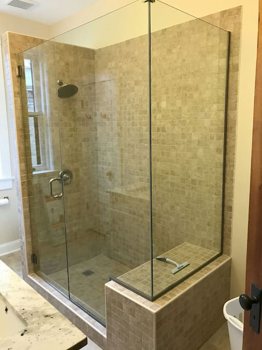 Newly redone bathroom with glass shower door.