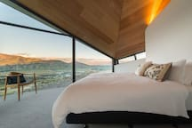 The master bedroom looks to the Clutha river and mountains beyond and, like the lounge area, has a 'tent fly' soaring ceiling, echoing the folds of the roof. Wooden privacy screens can block the light but many guests choose to wake to the view.