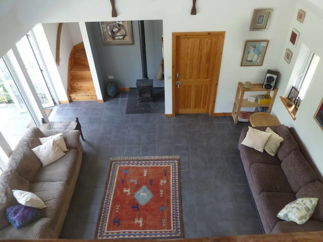 Living room as seen from mezzanine with underfloor heating and woodburner