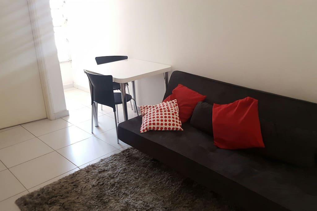 sala clara, com sofá-cama e mesa para 2
