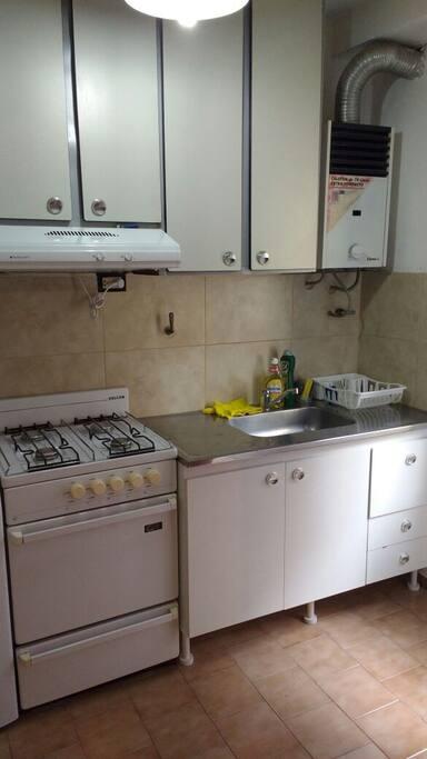 Cocina equipada con utensillos básicos necesarios para cocinar, ollas, colador abridor, cubiertos, vasos, espátula, jarro, rayador.-