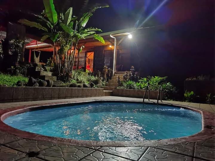 Cabaña con piscina rodeada de naturaleza.