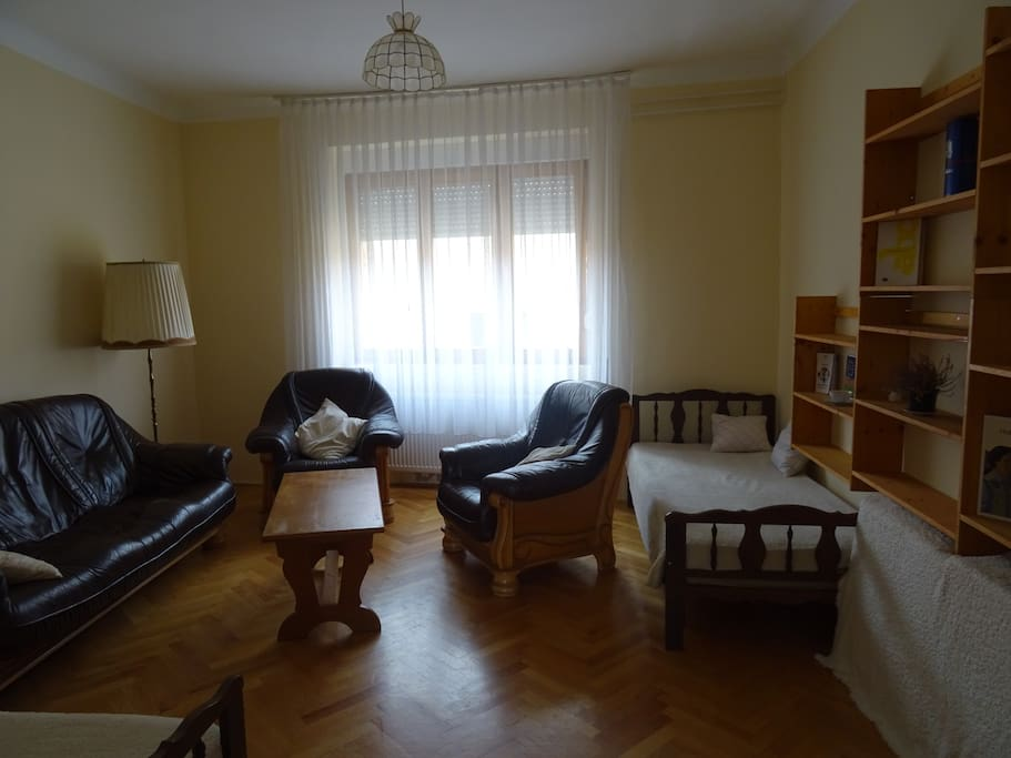 Tágas nappali bőrkanapéval, fotelekkel, két ággyal