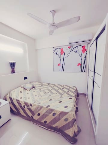 Bedroom with air conditioner, double bed and fully hydraulic storage, full height double door wardrobe, orthopaedic memory foam mattress with blanket and pillows.