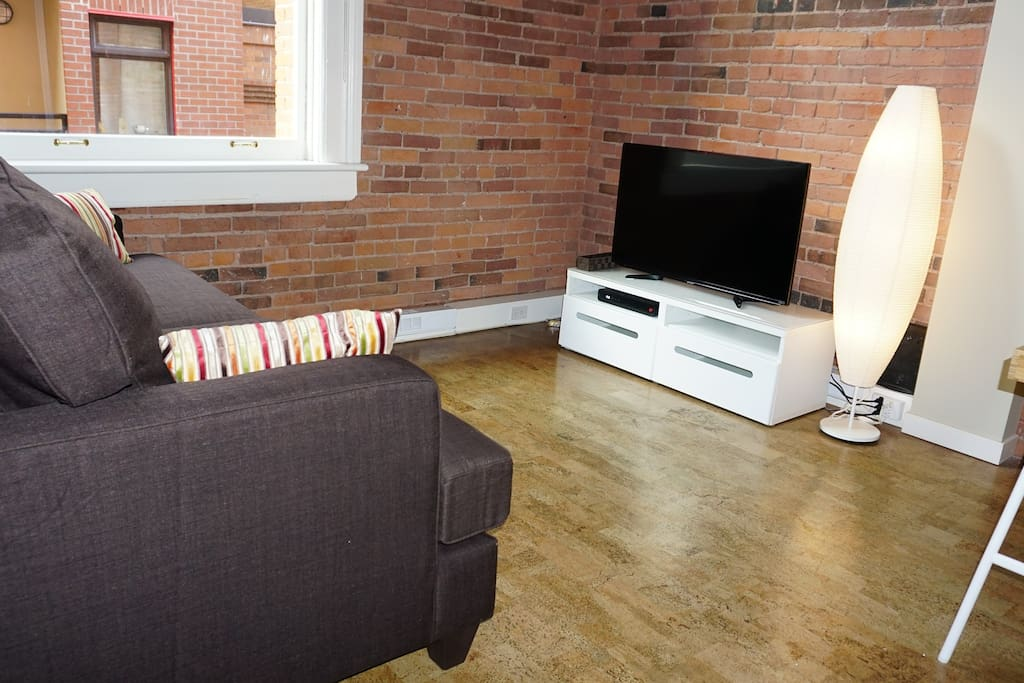 Spacious living room with gorgeous exposed brick
