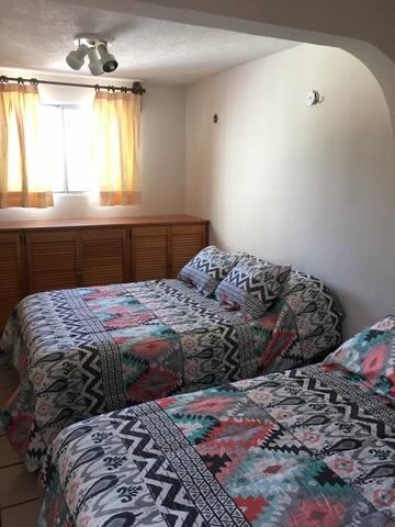 Habitación amplia con dos camas matrimoniales.