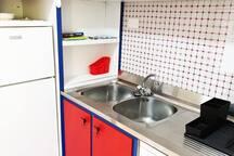 Cucina attrezzata. Secchiaio dotato di spugnette e scolappiatti e scolaposate in gomma nero