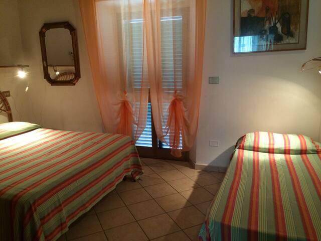 Camera con letto matrimoniale e lettino con porta finestra aprentesi sulla terrazza
