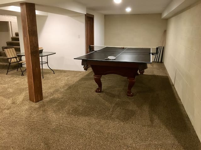 Basement with pool table and ping pong table, not bathroom in basement. Enter through the garage.
