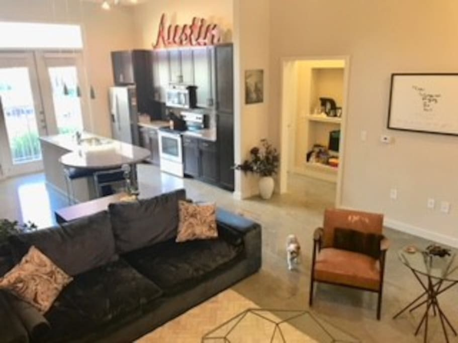 Large Open Concept living/kitchen area with huge comfy velvet couch for guests, and unique Austin decor.