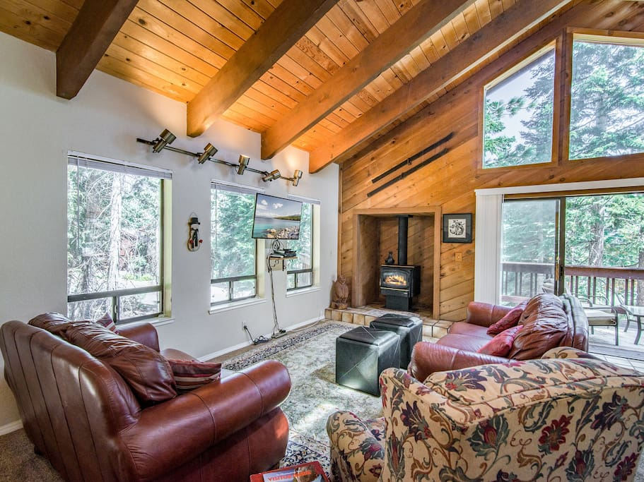 Lofted open beam wood ceilings and gas stove fireplace create a cozy ambience in the living room.