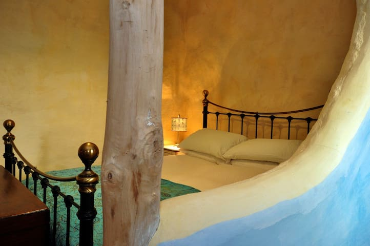 King sized bed and lime-rendered walls