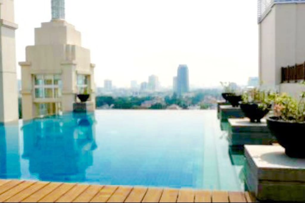 Outdoor rooftop infinity pool at noon with clear 360degrees view of Jakarta
